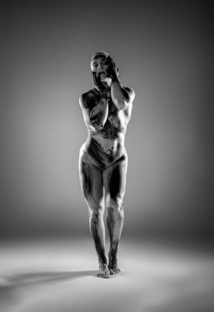 Very muscular naked athletic women on gray background.
