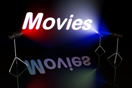 Movies sign on black background lit by multycolored lights
