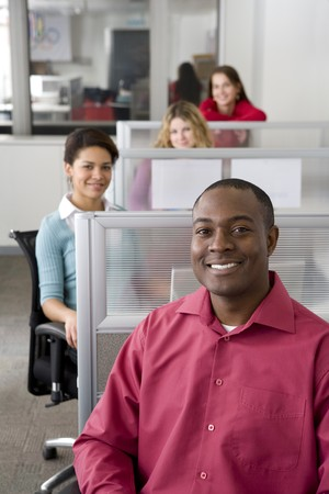 Businessman and co-workers sitting in cubicles photo