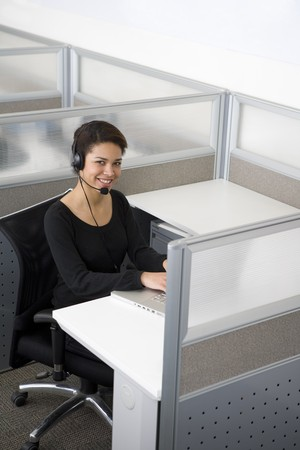 service desk: Businesswoman talking on headset in cubicle Stock Photo