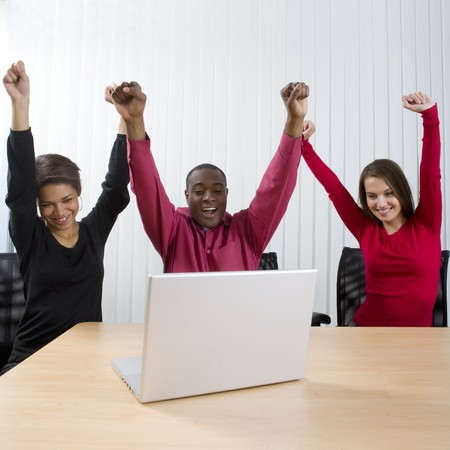 cheer: Co-workers looking at laptop and celebrating Stock Photo