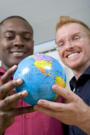 Multi-ethnic businessmen holding globe photo