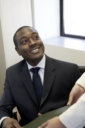 Businessman taking file from co-worker photo