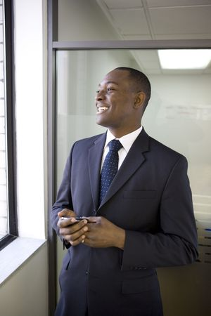 Businessman looking out office window photo