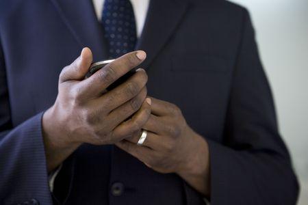 휴대 전화를 들고 사업가의 까이 서