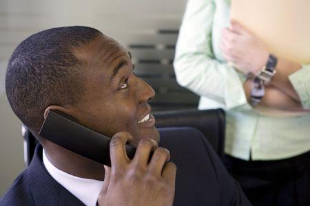 Businessman talking on office telephone photo