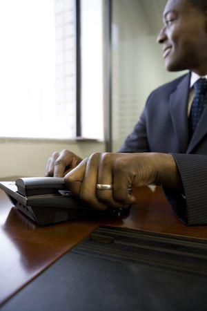 Businessman answering office telephone photo