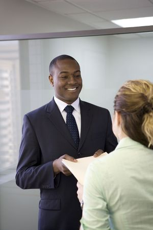 Businessman taking file from co-worker