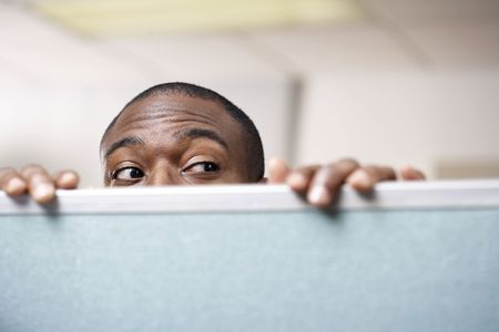 hidden: Businessman peeking over cubicle wall
