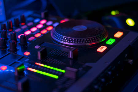 dj table with headphones mixing music flashy colors blue purple Banque d'images
