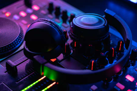 dj table with headphones mixing music flashy colors blue purple Reklamní fotografie