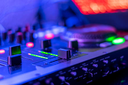 dj table with headphones mixing music flashy colors blue purple