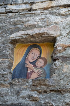 Mary holds Jesus child in her arms in a stone picture