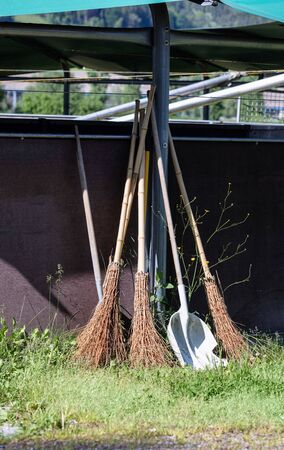 broom with silver shovel on a green meadow leaned against a brown wall 版權商用圖片