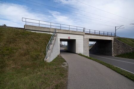 white concrete railway bridge with car and pedestrian underpass maximum high 2.90 meters wide angle view