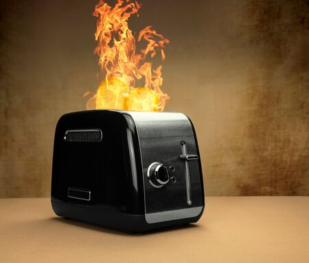 burning black silver toaster with big burning flames on top with baked ready toast on a brown table with brown structured background neutral silver colors