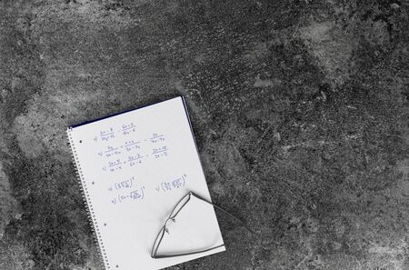 mathematics book with calculation tasks, glasses, on a grey marble table