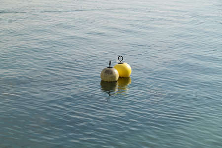 two water buoys floating in the water one white the other yellow plastic remains hang on the yellow buoy during the day in good weather without people