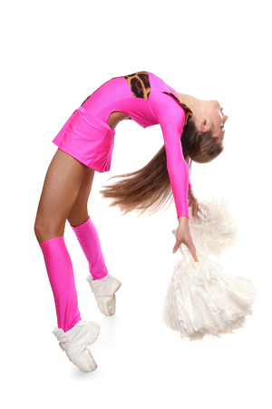 Cheerleader girl bends with pom-pom. Pretty flexible girl pink leo costume photo