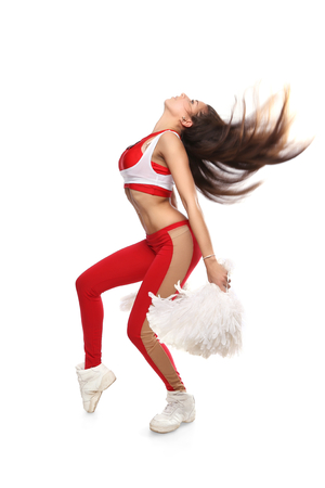 Cheerleader girl waving hair with pom-pom. Pretty flexible girl standing on white photo