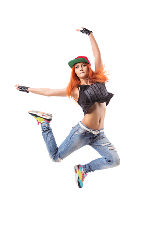 fingerless gloves: Modern hip-hop dance girl jumping on isolated background. Young teenager with jeans. cap and fingerless gloves Stock Photo