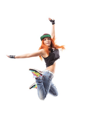 fingerless gloves: Modern hip-hop girl jumping on isolated background. Young teenager with jeans. cap and fingerless gloves