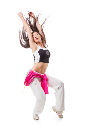 Female in white sweatpants and a pink hoodie and sneakers standing on isolated white background.