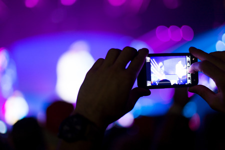 Close up of photographing with smartphone during a concert photo