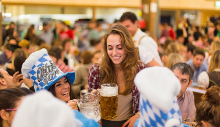 young girls toast with Oktoberfest beer Editorial