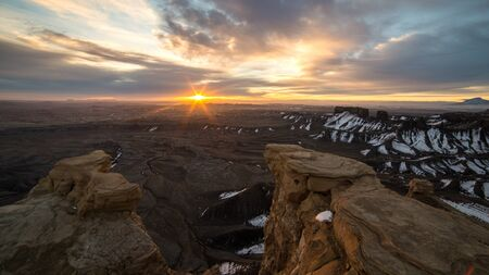 Sun peaking over the horizon lighting up the Utah desert from the Skyline overlook in Caineville during a colorful sunrise on the edge of a cliff.