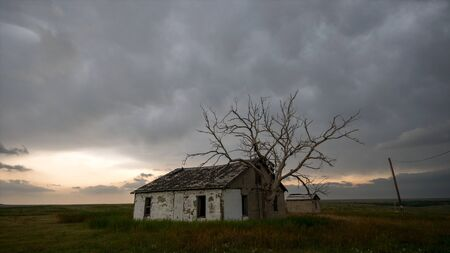 Old rundown house with storm clouds overhead in the plains of Colorado. Foto de archivo
