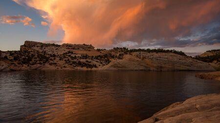 Colorful sunset reflecting in desert lake at Red Fleet Reservoir in Utah.