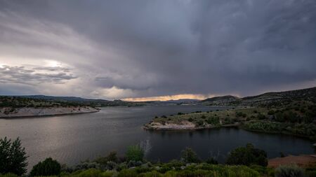 Storm blowing over lake with dark clouds through the sky.