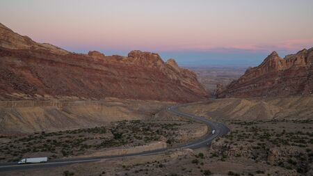 Viewing traffic on I-70 through the San Rafael Swell with light on the cliffs. Banque d'images