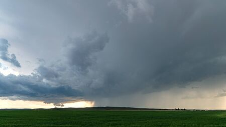 Tornado touching ground behind rainstorm in Nebraska in wide view of severe storm. Stock Photo