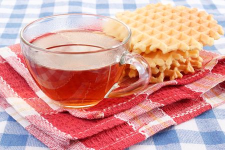 Glass cup of tea with waffles