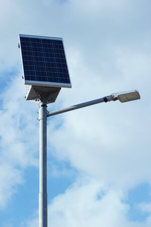 Pillar with electric solar panel and street lighting lamp system. Modern street equipment with renewable energy save technology. 스톡 콘텐츠