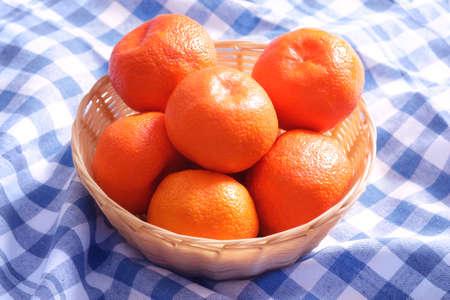 Heap of fresh tangerines mandarins in wicker basket on tablecloth napkin