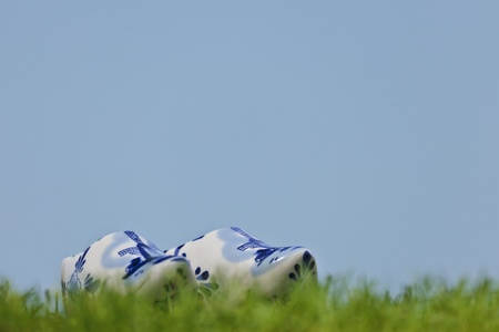 A set of Dutch porcelain clogs in white and blue on fresh green grass. The clogs are a typical Dutch souvenir. Stock Photo - 11479607