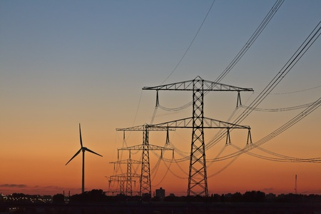 Silhouettes of a wind turbine and electric power posts during sunset photo