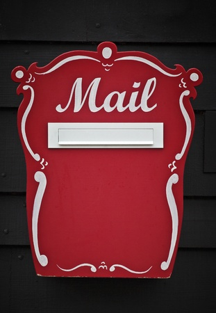 A traditional, red wooden handcrafted mailbox with the letters Mail handpainted on the front photo