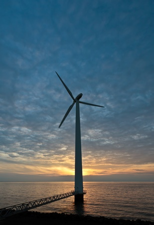 The sun disappears just behind a windturbine along the seashore at sunset Stock Photo - 12983094