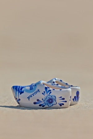 delftware: Small porcelain Dutch clogs on the beach with Holland written on it Stock Photo