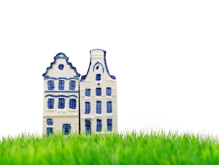 Delft blue miniature Amsterdam canal houses on fresh green grass with a white background photo