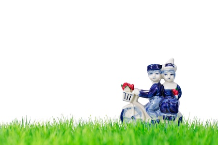 Dutch souvenir man and woman on a bicycle with grass in front Stock Photo - 13930045