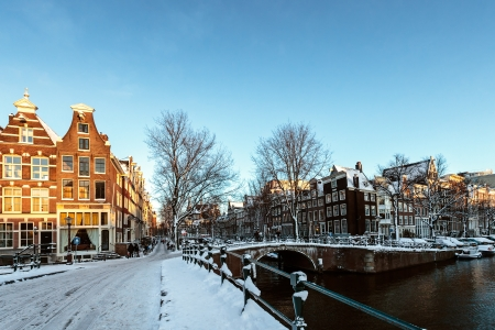Snow has fallen in Amsterdam; the streets are covered with snow and the sun makes the canal houses glow orange Stock Photo