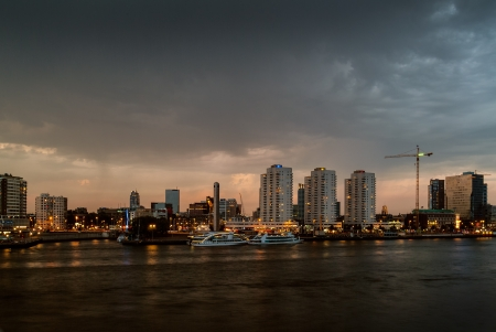 nighttime: Skyline of Rotterdam in the evening with the central river in front