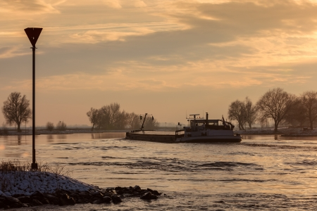 Dutch riverboat transporting goods during winter on the river IJssel photo