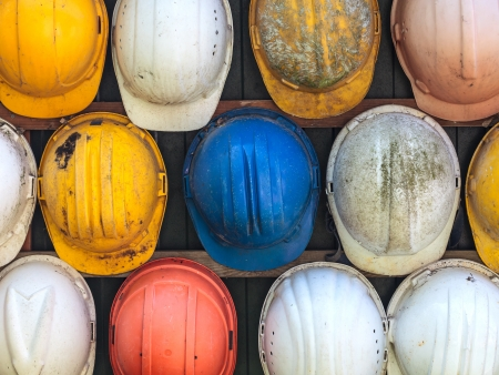 Old and worn colorful construction helmets Stock Photo