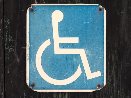 Old weathered wheelchair sign for the handicapped on a black wooden wall photo